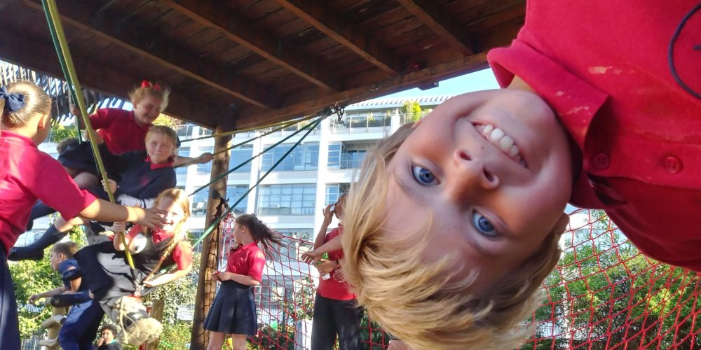 boy hanging upside-down from climbing frame