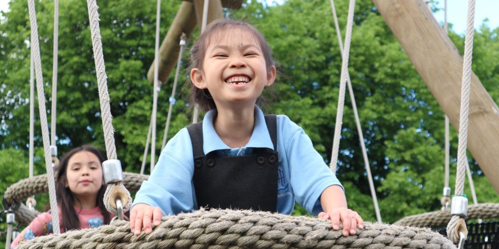 Girl at adventure playground, playing on swing and smiling