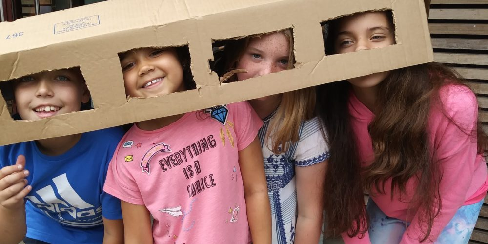 Four children with cut out cardboard boxes on them