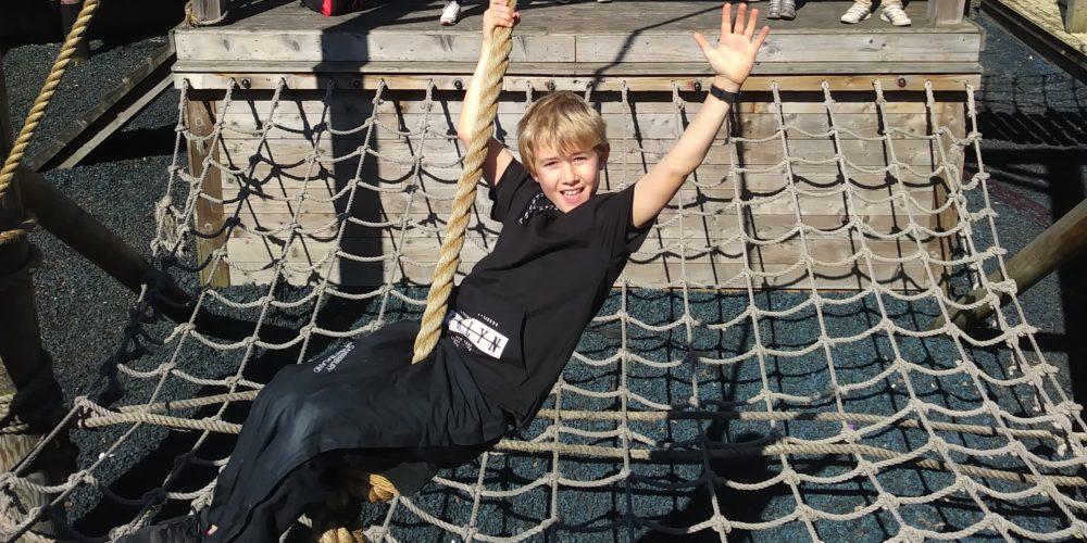 Boy on rope swing waving
